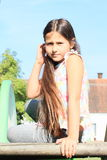 Girl sitting on a slide Stock Photo