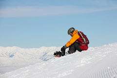 Girl sitting on a slope and prepares a snowboard Stock Images