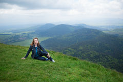 Girl sitting on the slope of volcano in Auvergne Royalty Free Stock Image