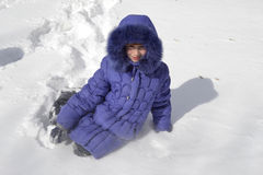 Children in winter. Girl sitting in the snow Royalty Free Stock Images