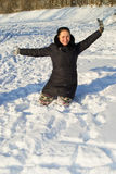 Girl sitting in the snow. On a clear sunny day royalty free stock photography