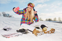 Girl  sitting on the snow and is making a selfie Royalty Free Stock Photo