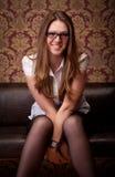Girl sitting on sofa Stock Photos