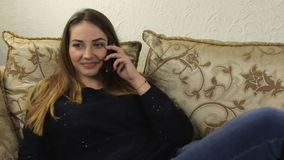 Girl sitting on a sofa accepts a phone call stock video