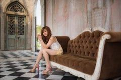 Girl sitting on sofa Stock Photography
