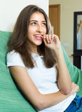 Girl sitting at sofa and biting nails Stock Photo