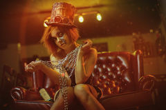 Girl sitting on sofa with chains in hands and hat. Stock Photography
