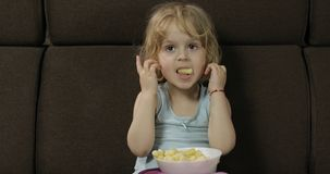 Girl sitting on sofa and eating corn puffs. Child taste puffcorns stock image