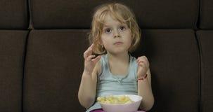 Girl sitting on sofa and eating corn puffs. Child watching tv, taste puffcorns