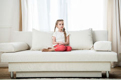 Girl sitting on sofa at home Stock Photo