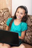 The girl sitting on the sofa with laptop Royalty Free Stock Images