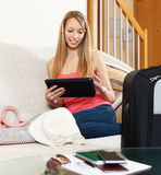 Girl sitting on sofa near luggage Royalty Free Stock Image
