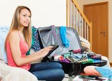Girl sitting on sofa near luggage Stock Photos