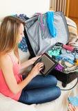 Girl sitting on sofa near luggage Stock Image