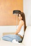 Girl sitting on sofa next to lamp Stock Photo