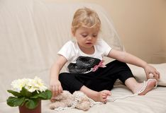 Girl sitting on a sofa and playing with beads Stock Photos