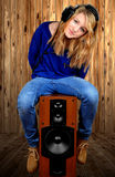 The girl sitting on the speaker. On wooden background Stock Photography