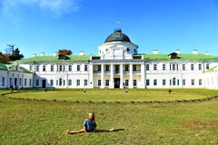 Girl sitting on the splits in the background of a large palace Stock Images