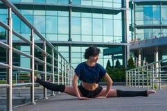 Girl sitting on the splits. Dance outdoor. Girl sitting on the splits, with one foot on a metal fence. Beautiful girl performs acrobatics. ballerina in casual Stock Photos