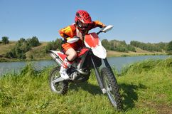 Girl sitting on a sport bike for motocross. The girl in the red shirt, helmet and boots, sitting on a sport bike, amid lakes and forests Stock Photos