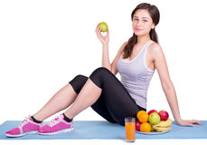 Girl sitting on sport mat next to fruit Royalty Free Stock Photo