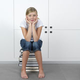 Girl sitting on a stack of books royalty free stock photography