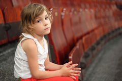 Girl sitting on stair near armchairs in circus. Little girl sitting on stair near armchairs in circus and looking at camera Royalty Free Stock Photo
