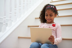 Girl Sitting On Staircase Using Digital Tablet Royalty Free Stock Photography