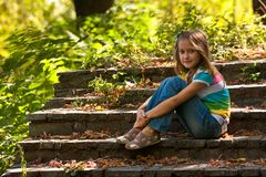 Girl sitting on a stairs. Little smiling girl sitting on a stairs Royalty Free Stock Image