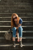 Girl sitting on the stairs with a bag. Red-haired girl sitting on the stairs with a bag Royalty Free Stock Image