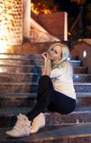 Girl that sitting on the stairs in casual (night). Girl in leggins and sneakers are sitting on the stairs in the evening Stock Photos
