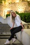 Girl that sitting on the stairs in casual (night). Girl in leggins and sneakers are sitting on the stairs in the evening Stock Image