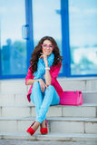 Girl sitting on stairs in colorful clothes Royalty Free Stock Image