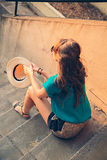 Girl sitting on the stairs. And holding her hat Royalty Free Stock Images