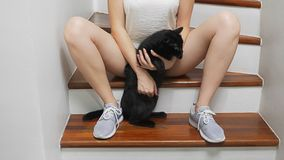 The girl is sitting on the stairs in the house between her legs is holding a black cat and stroking it stock photo