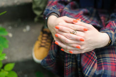 Girl sitting on the stairs in park. Girl sitting on the stairs in the park. Hands folded in her lap. Orange manicure on her nails Royalty Free Stock Image