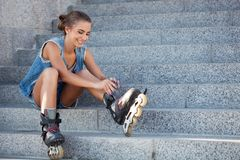 Girl sitting on the stairs and puts on skates Stock Photos