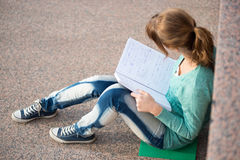 Girl sitting on stairs and reading note Stock Image