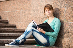 Girl sitting on stairs and reading note Royalty Free Stock Photo
