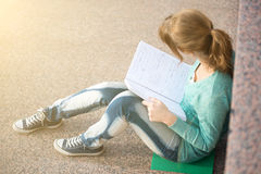 Girl sitting on stairs and reading note Stock Photography