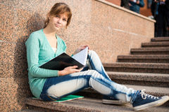 Girl sitting on stairs and reading note. Portrait of a beautiful teenage student girl sitting on stairs in park with copy book and studing. Sunny summer day Stock Photos
