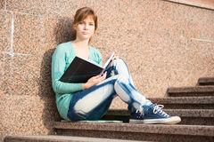 Girl sitting on stairs and reading note Royalty Free Stock Photography