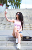 Girl sitting on stairs, in the street makes your phone beautiful self Stock Photos