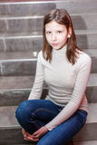 Girl sitting on stairs. Teen girl sitting on stairs. Indoor portrait of a sad teenage girl Stock Image