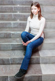 Girl sitting on stairs. Teen girl sitting on stairs. Indoor portrait of a sad teenage girl Stock Photos