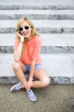 Girl sitting on stairs using mobile phone Stock Images