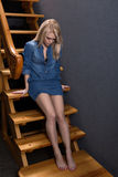 Girl sitting on the stairs wooden stairs. Girl sits on a wooden ladder and looking down Royalty Free Stock Photography
