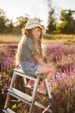 Girl sitting on a stepladder in fairy field of lavender. Stock Images