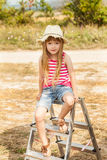 Girl sitting on a stepladder outdoor. Royalty Free Stock Photography