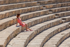 Girl is sitting on the steps of amphitheater Stock Photo